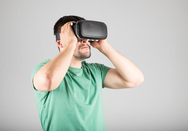 Giovane che per mezzo della cuffia avricolare di realtà virtuale isolata Foto Premium