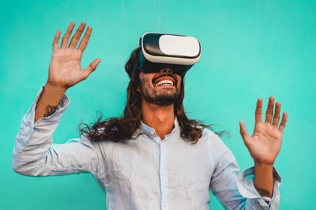 Giovane che utilizza le cuffie da realtà virtuale con la parete blu sullo sfondo - ragazzo alla moda che si diverte con la nuova tecnologia di tendenza - tecnologia, divertimento e concetto futuro - focus sulla bocca maschile e occhiali vr Foto Premium