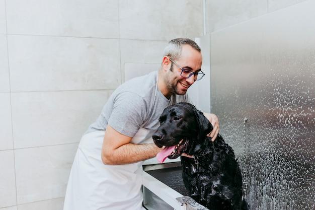 Giovane che lava e che pulisce un labrador nero nel salone governare. animali puliti e concetto sano. Foto Premium