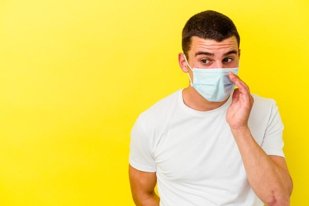 Il giovane che indossa una protezione per il coronavirus isolato sul muro giallo sta dicendo una notizia segreta sulla frenata e guarda da parte Foto Premium