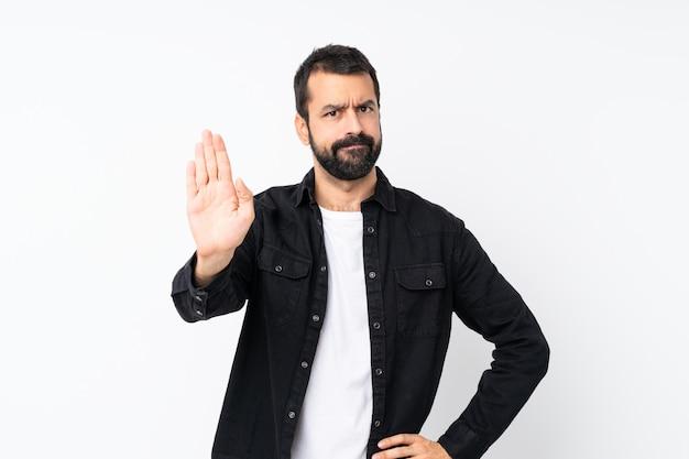 Giovane con la barba sopra gesto di fabbricazione bianco isolato di arresto Foto Premium