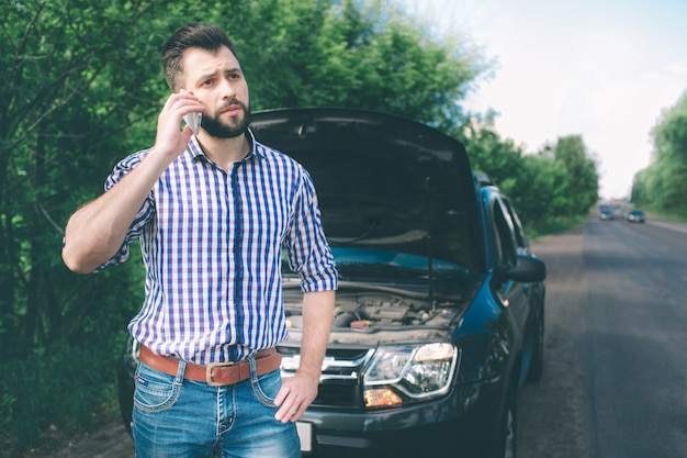 Un giovane con un'auto nera che si è rotta sulla strada e chiede che arrivi il tecnico Foto Premium