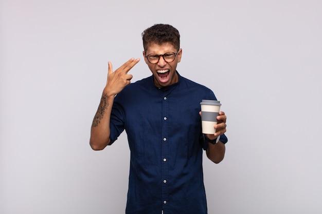 Giovane con un caffè che sembra infelice e stressato, gesto di suicidio che fa il segno della pistola con la mano, indicando la testa Foto Premium