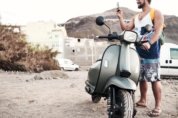 Giovane uomo con la moto messaggistica con il telefono Foto Premium