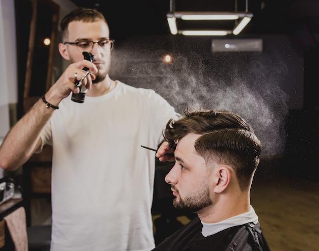 Giovane con taglio di capelli alla moda al negozio di barbiere. il barbiere fa taglio di capelli e barba. Foto Premium