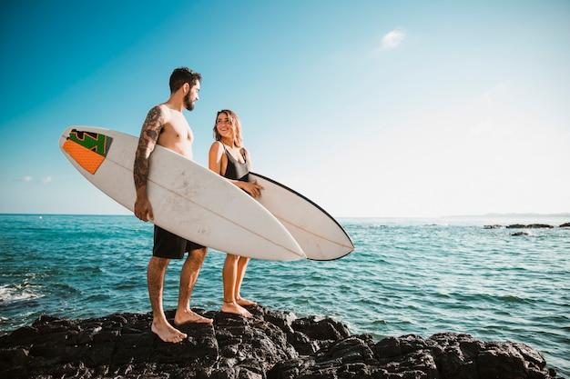 Giovane uomo e donna con tavole da surf sulla roccia vicino al mare Foto Premium