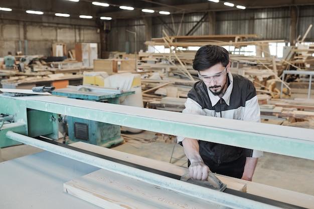 Giovane uomo in abiti da lavoro chinarsi sul banco di lavoro e levigare la superficie del pezzo in lavorazione con utensile manuale in legno mentre si lavora in fabbrica Foto Premium