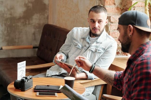 Giovani uomini seduti nella caffetteria dell'hotel e bevendo caffè mentre discutono di idee per il servizio fotografico Foto Premium