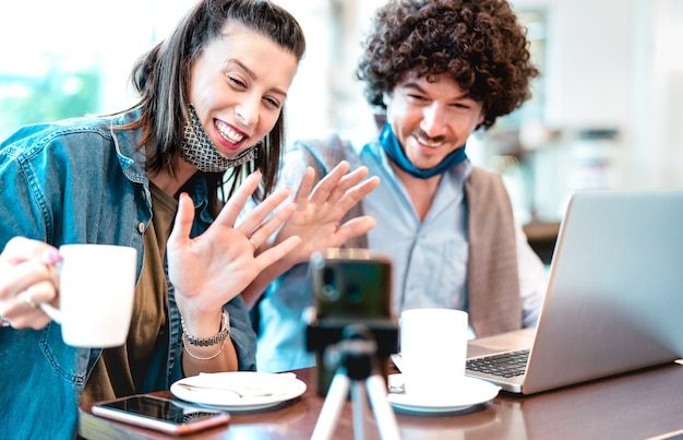 Giovane coppia millenaria condivisione di contenuti creativi con maschera facciale Foto Premium