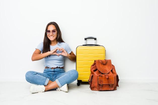 Giovane donna indiana di razza mista pronta ad andare a viaggiare sorridendo e mostrando una forma di cuore con le mani. Foto Premium
