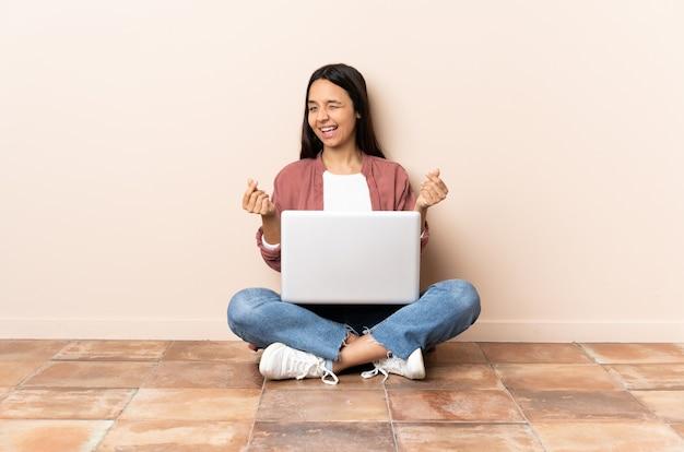 Giovane donna di razza mista con un computer portatile seduto sul pavimento che fa gesto di soldi Foto Premium