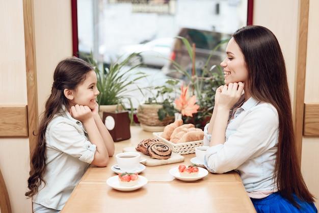 Giovane mamma con figlia mangiare torte in caffetteria. Foto Premium