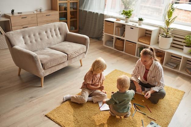 Giovane madre seduta sul tappeto insieme ai suoi figli giocano e disegnano in soggiorno Foto Premium