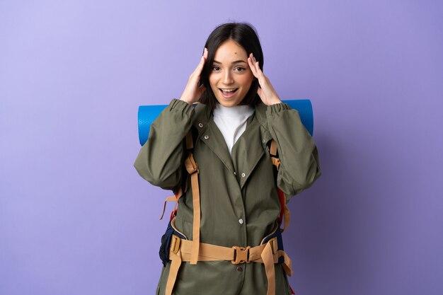 Giovane donna alpinista con un grande zaino con espressione di sorpresa Foto Premium