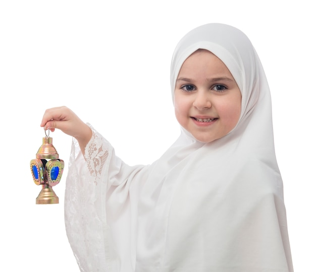 Giovane ragazza musulmana in hijab bianco con lanterna Foto Premium
