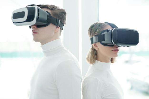 Giovani in maglioni bianchi che indossano occhiali per realtà virtuale in piedi schiena contro schiena Foto Premium