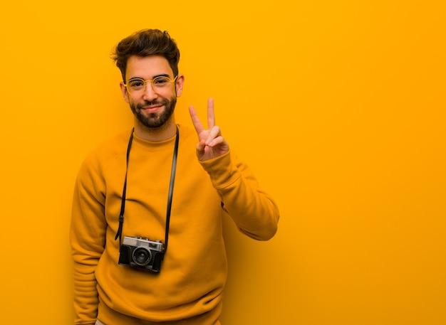 Uomo giovane fotografo che mostra il numero due Foto Premium