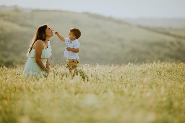 Madre incinta dei giovani con il suo ragazzino sveglio nel campo il bello giorno soleggiato Foto Premium