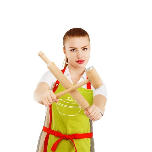 Giovane e graziosa casalinga con un mattarello e un martello di carne nelle sue mani Foto Premium