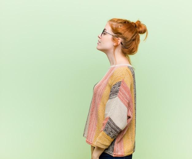 Giovane donna capa abbastanza rossa sulla vista di profilo che cerca di copiare spazio avanti, pensando, immaginando o sognando ad occhi aperti contro la parete verde Foto Premium