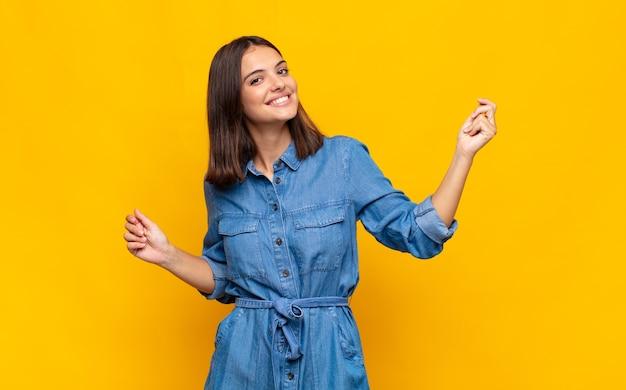 Giovane bella donna sorridente, spensierata, rilassata e felice, ballare e ascoltare musica, divertirsi a una festa Foto Premium