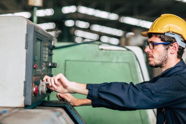 Il giovane ingegnere tecnico di professione fa funzionare la macchina pesante al cnc automatizzato in fabbrica, mano del lavoratore del primo piano. Foto Premium
