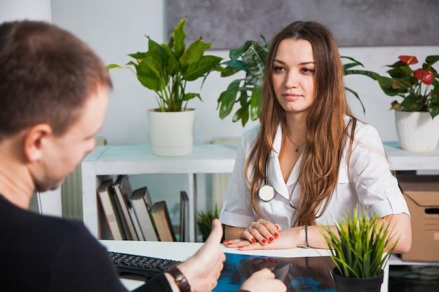 Giovane medico femminile professionista che parla al paziente all'ospedale. consultare un malato, fare prescrizioni. concetto di diagnostica di medicina sanitaria Foto Premium