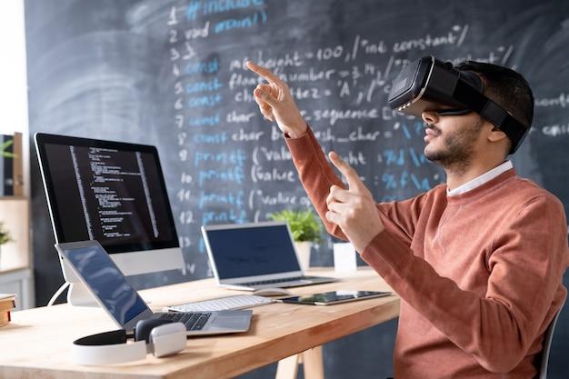 Giovane programmatore durante il test delle cuffie vr o la presentazione di nuovo software mentre indica il display virtuale sul posto di lavoro Foto Premium