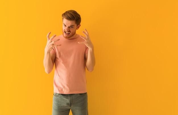 Giovane uomo della testarossa arrabbiato e sconvolto Foto Premium
