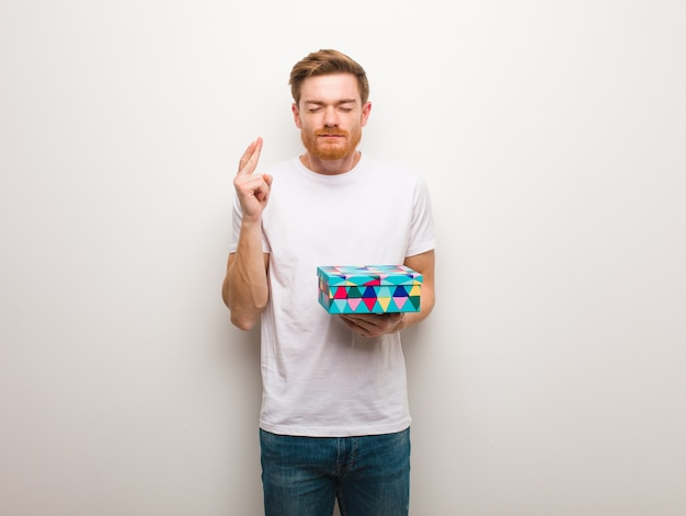 Giovane uomo di redhead dita incrociate per avere fortuna. tenendo una confezione regalo. Foto Premium