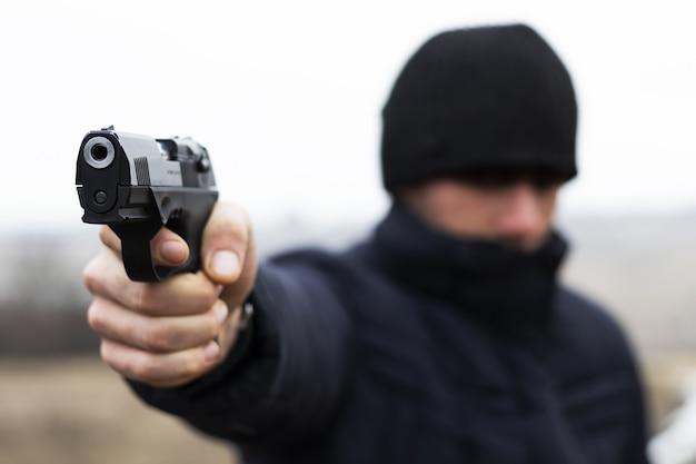 Il giovane ladro spara a un concetto criminale del primo piano della pistola Foto Premium