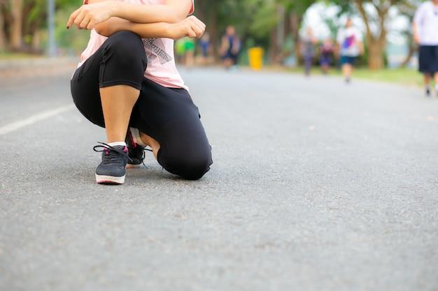 Giovane donna del corridore che riposa sulla strada. Foto Premium