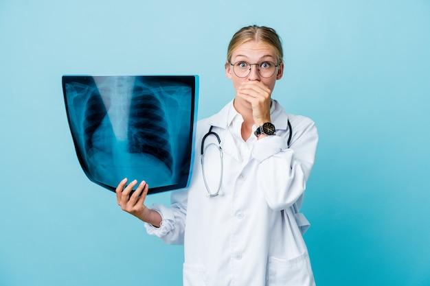 Giovane donna russa del medico che tiene una scintigrafia ossea sulla bocca della copertura scioccata blu con le mani Foto Premium