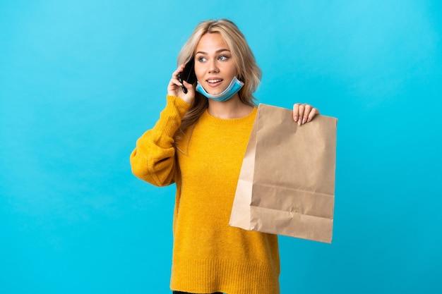 Giovane donna russa in possesso di un sacchetto della spesa isolato sulla parete blu mantenendo una conversazione con il telefono cellulare Foto Premium