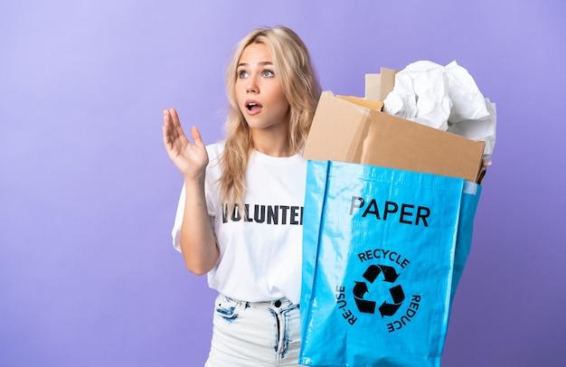 Giovane donna russa che tiene un sacchetto di riciclaggio pieno di carta da riciclare isolato su viola con espressione facciale sorpresa Foto Premium