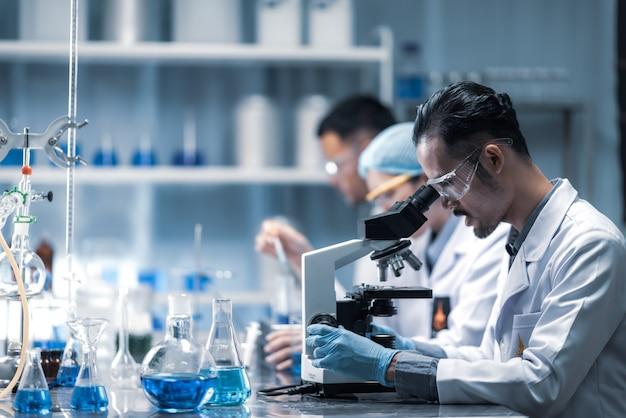 Giovane scienziato che osserva tramite un microscopio in un laboratorio. giovane scienziato che fa delle ricerche. Foto Premium