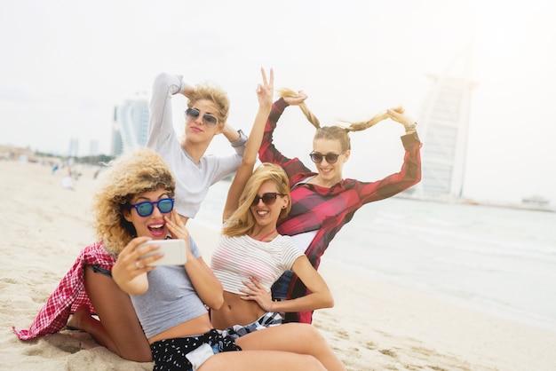 Giovani amiche sexy divertendosi e prendendo selfie sulla spiaggia. divertimento estivo da ragazza. Foto Premium