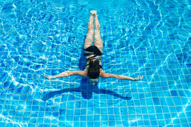 Giovane donna esile sexy che si rilassa nella piscina con acqua blu di cristallo Foto Premium