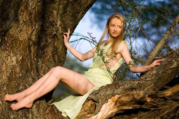 Giovane donna sexy in vestito verde che si siede sul tronco di albero sopra l'acqua il giorno di estate con la natura verde al fondo Foto Premium