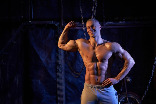 Giovane uomo muscoloso torso nudo in piedi tra catene di metallo, guardando seriamente la fotocamera, lo spazio della copia con le spalle alla telecamera mostra i bicipiti Foto Premium