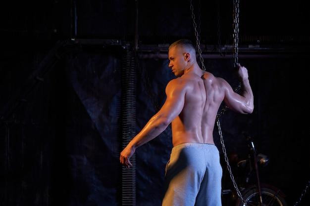 Giovane uomo muscoloso torso nudo in piedi tra catene di metallo, guardando seriamente la fotocamera, copia lo spazio con le spalle alla telecamera Foto Premium