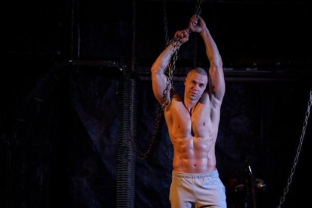 Giovane uomo muscoloso torso nudo in piedi tra catene metalliche, guardando seriamente la fotocamera, copia dello spazio Foto Premium