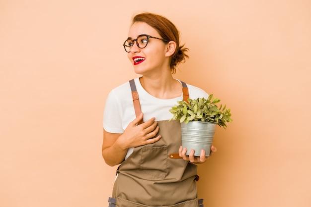 La giovane donna araba magra del giardiniere guarda da parte sorridente, allegra e piacevole. Foto Premium