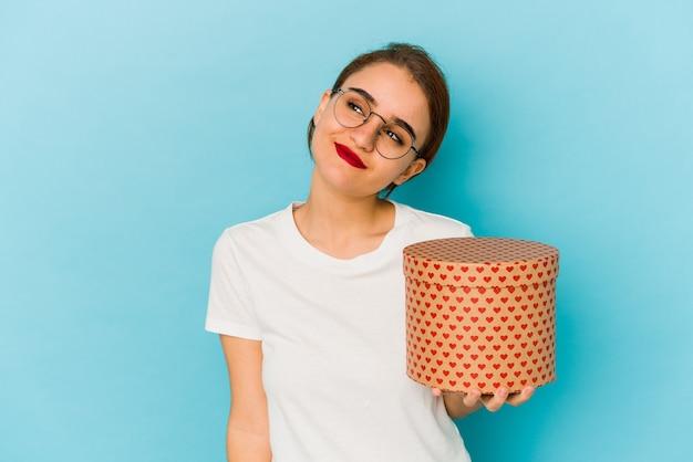Giovane ragazza araba magra che tiene una scatola di san valentino sognando di raggiungere obiettivi e scopi Foto Premium