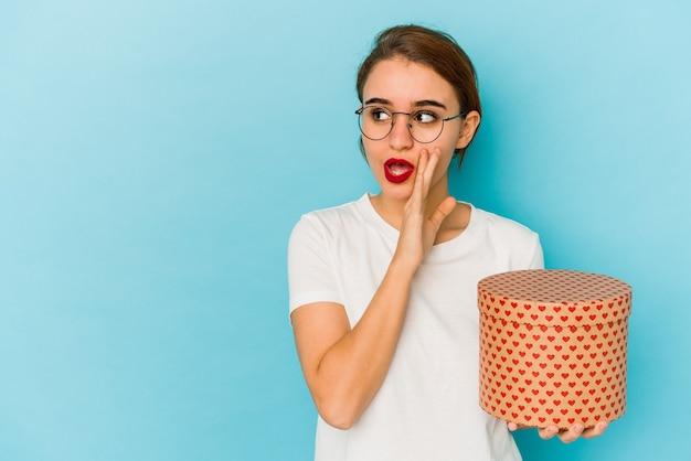 La giovane ragazza araba magra che tiene una scatola di san valentino sta dicendo una notizia segreta di frenata calda e sta guardando da parte Foto Premium