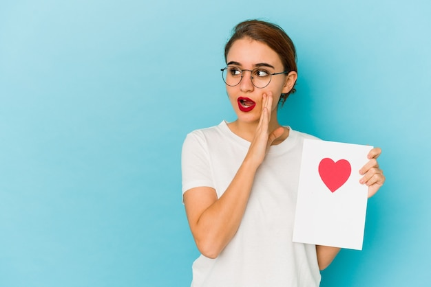La giovane ragazza araba magra che tiene una carta di san valentino sta dicendo una notizia segreta di frenata calda e sta guardando da parte Foto Premium