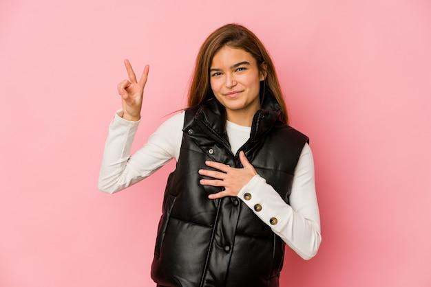 Giovane ragazza adolescente caucasica magra prestando giuramento, mettendo la mano sul petto. Foto Premium