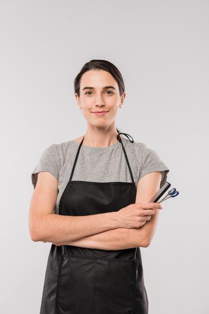 Giovane parrucchiere femminile sorridente in abiti da lavoro che tiene spazzola per capelli e forbici e ti guarda in isolamento Foto Premium