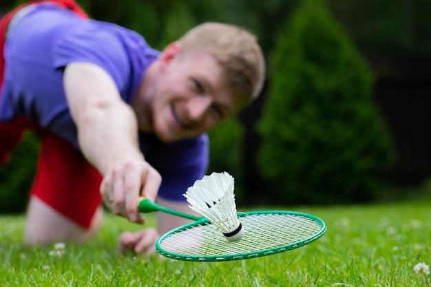 Uomo di sport forte sorridente dei giovani che gioca badminton con la racchetta e il volano. montare il giocatore di badminton atleta maschio vola sopra l'erba nel salto, azione, movimento, movimento. concetto di attacco e difesa Foto Premium