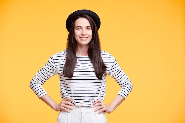 Giovane donna sorridente in abbigliamento casual mantenendo le mani sulla vita mentre posa sul muro giallo in isolamento Foto Premium
